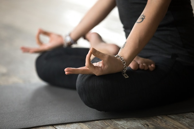 Young woman doing padmasana exercise, mudra gesture close up