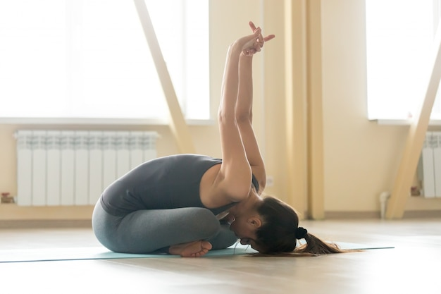 Young woman doing padmasana pose with forward bend, interior bac