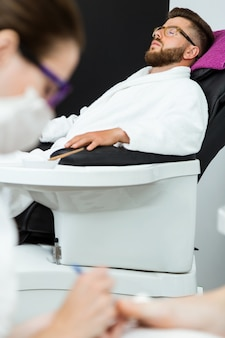 Young woman doing pedicure in salon. beauty concept.