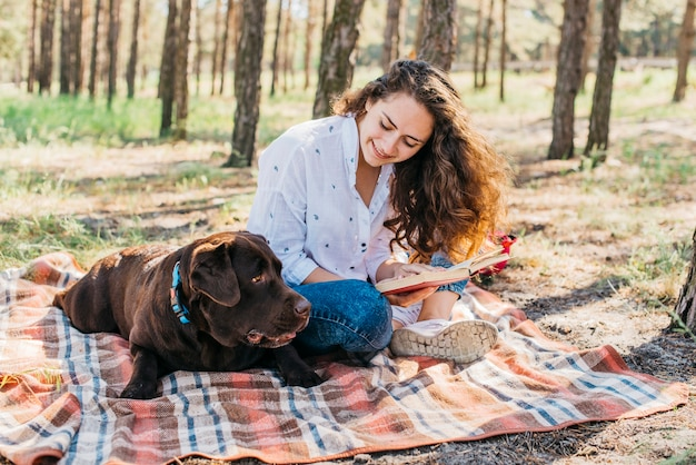 Young woman doing a picnic with her dog