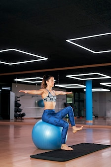 Young woman doing pilates exercises on fitness ball in a modern gym.