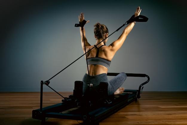 ピラティスを行う若い女性は、リフォーマーベッドで運動します。美しいスリムなフィットネストレーナー。フィットネスの概念