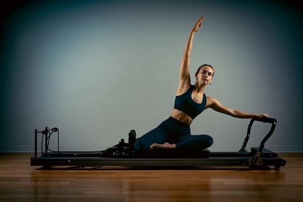 필 라 테 스를 하 고 젊은 여자는 개혁 자 침대와 함께 연습. 아름다운 슬림 피트니스 트레이너