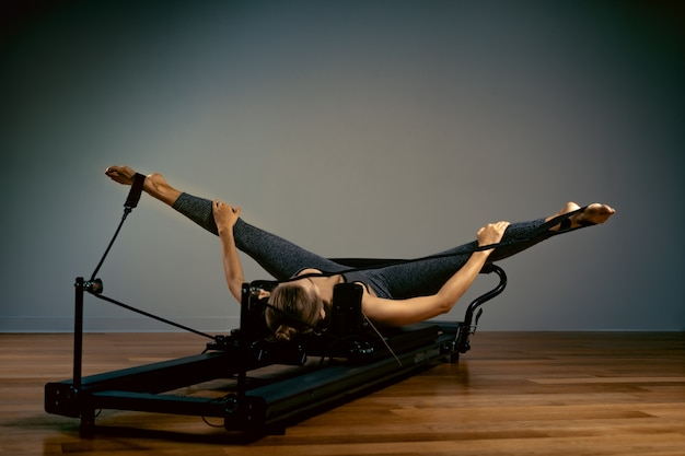 Young woman doing pilates exercises with a reformer bed. beautiful slim fitness trainer