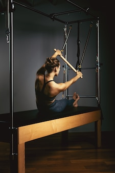 Young woman doing pilates exercises with a reformer bed