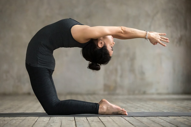 Young woman doing preparation for kapotasana