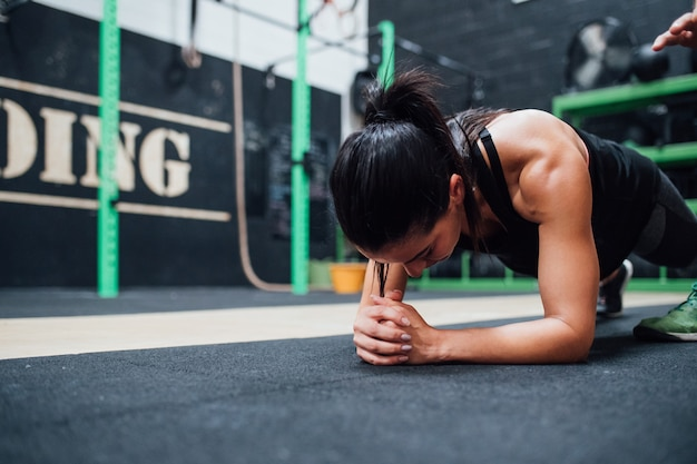 Young woman doing push ups training indoor gym