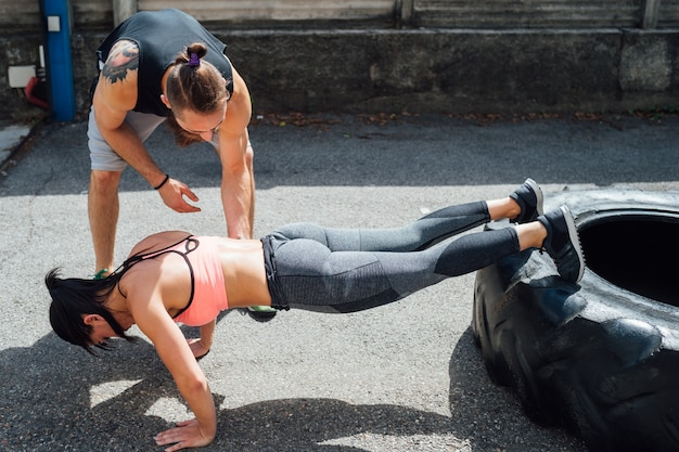 Young woman doing push ups training outdoor using giant tyre