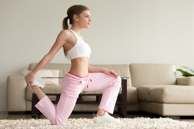 Young woman doing quad stretches at home