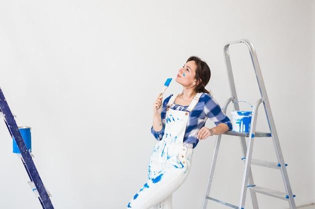 Молодая женщина делает косметический ремонт над белой стеной.
