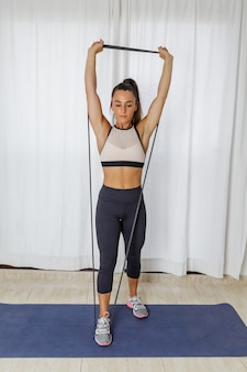 Young woman doing resistance exercise for shoulders