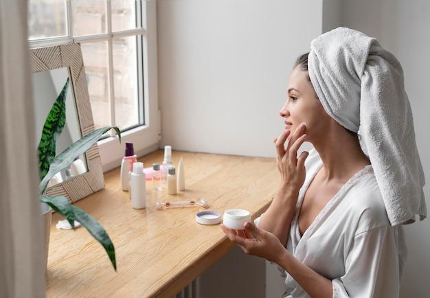 Giovane donna che fa una routine di cura di sé a casa Foto Gratuite