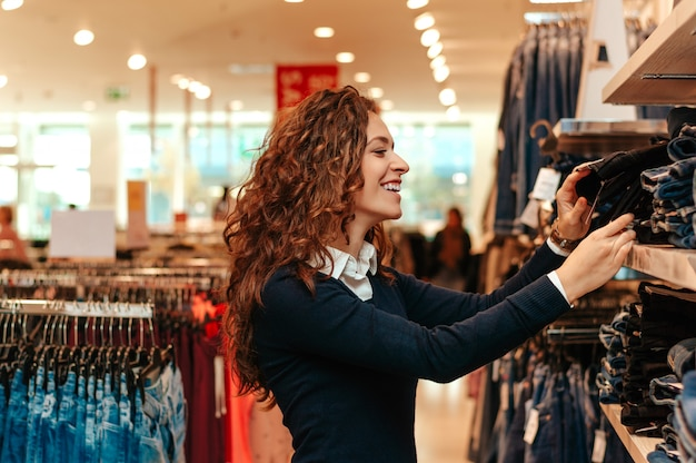 Young woman doing shopping and choosing clothes.