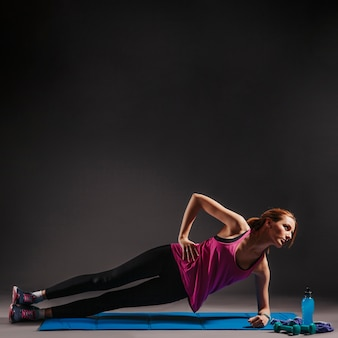 Young woman doing side plank