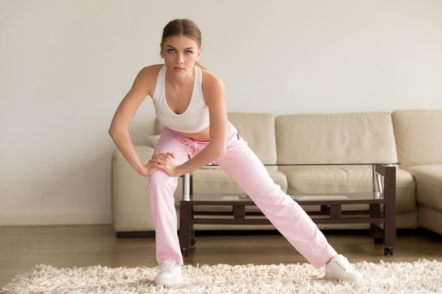 Young woman doing simple morning exercises at home