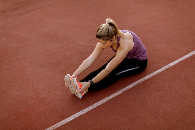 Young woman doing some exercises and streching legs at the court at outdoor
