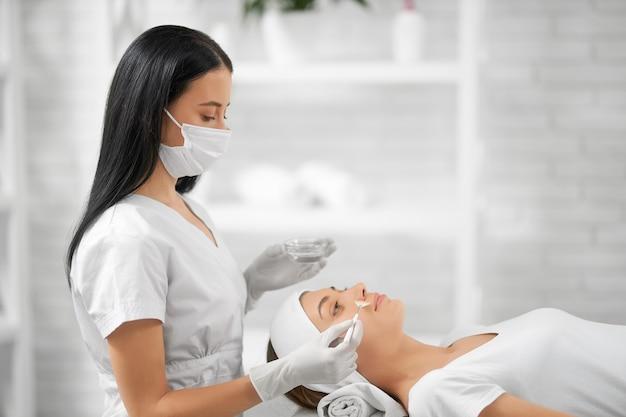 Giovane donna che fa procedura speciale per i miglioramenti della pelle