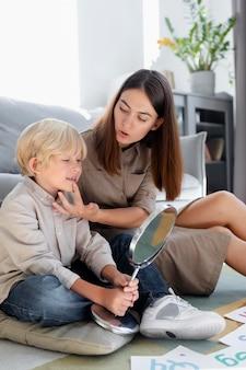 어린 금발 소년과 언어 치료를 하는 젊은 여자