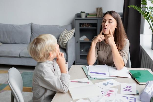 Молодая женщина делает логопед с маленьким мальчиком