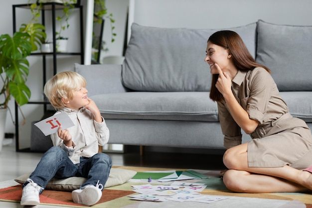 어린 소년과 언어 치료를 하는 젊은 여자
