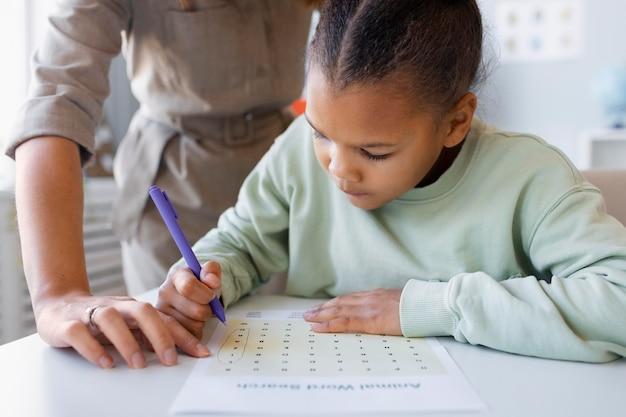 小さな女の子と言語療法をしている若い女性