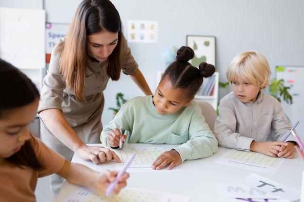 그녀의 클리닉에서 아이들과 언어 치료를 하는 젊은 여성