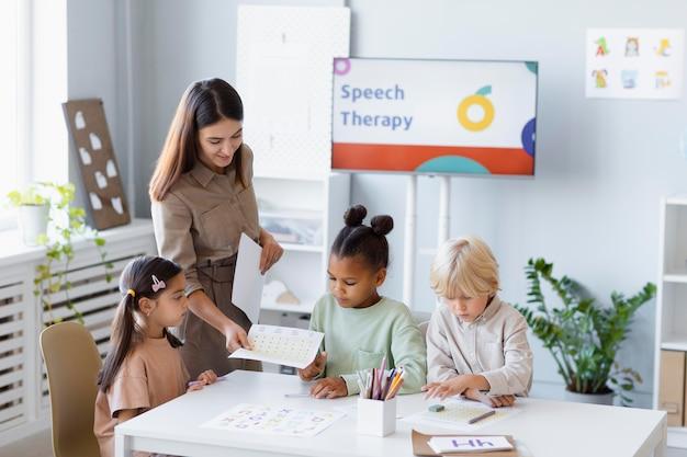 아이들과 언어 치료를 하는 젊은 여성