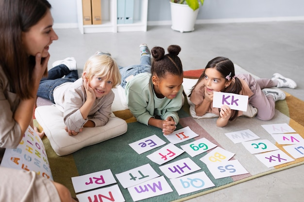 Young woman doing speech therapy with children
