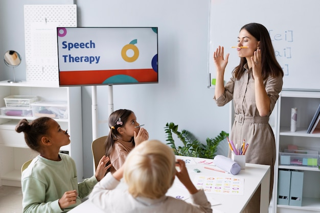 Young woman doing speech therapy with kids