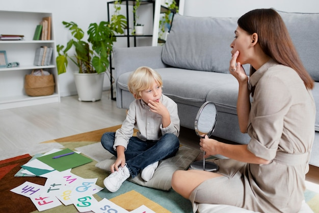 Young woman doing speech therapy with a little blonde boy
