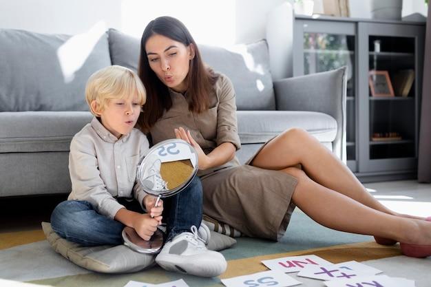 Giovane donna che fa logopedia con un ragazzino biondo