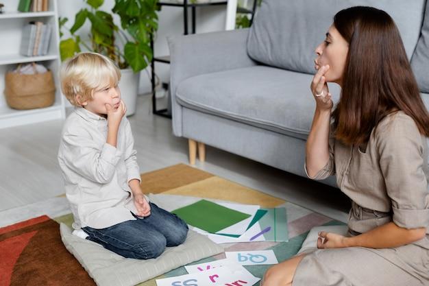 Giovane donna che fa logopedia con un ragazzino