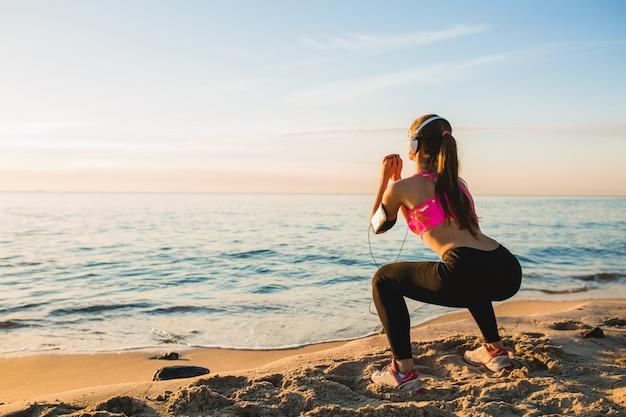 朝日の出ビーチでスポーツ演習を行う若い女性