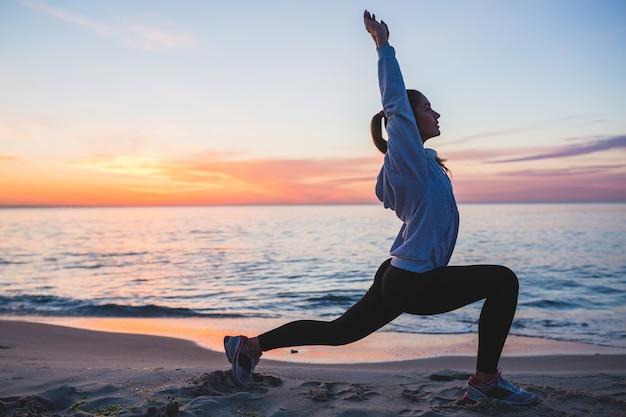 Молодая женщина делает спортивные упражнения на пляже восхода солнца утром