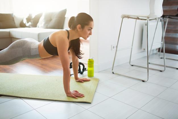 検疫中に部屋でスポーツトレーニングをしている若い女性。完全な長さの板の位置にあるフィットネスモデルスタンドのカットビュー。強い女性の表情は部屋で運動します。