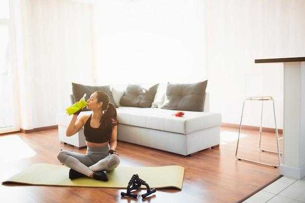 検疫中に部屋でスポーツトレーニングを行う若い女性。組んだ足でマットの上に座り、緑の瓶からタンパク質を飲みます。トレーニングの後は、リラックスして休憩してください。