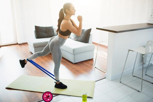 検疫中に部屋でスポーツトレーニングをしている若い女性。ヨガマットの上に立ち、レジスタンスバンドを使って背中の脚を伸ばします。