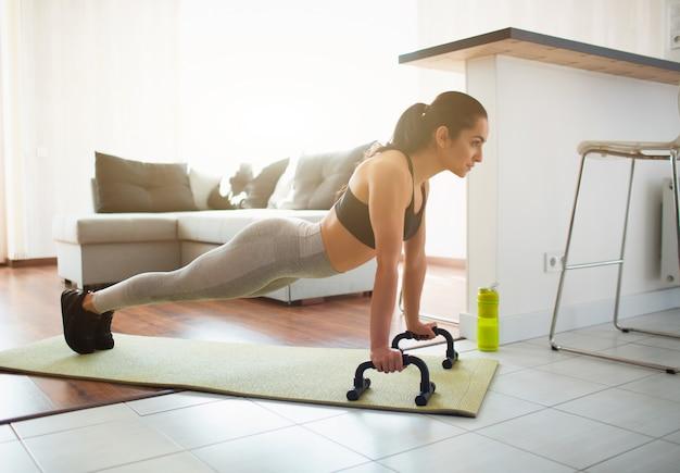 Молодая женщина делает спортивные тренировки в комнате во время карантина