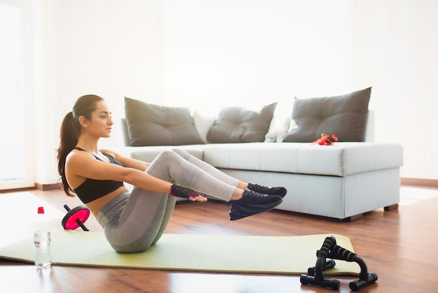Young woman doing sport workout in room during quarantine. girl doing abs exercise. hold legs in air and hands parallel towards floor. keeping body toned and fit.