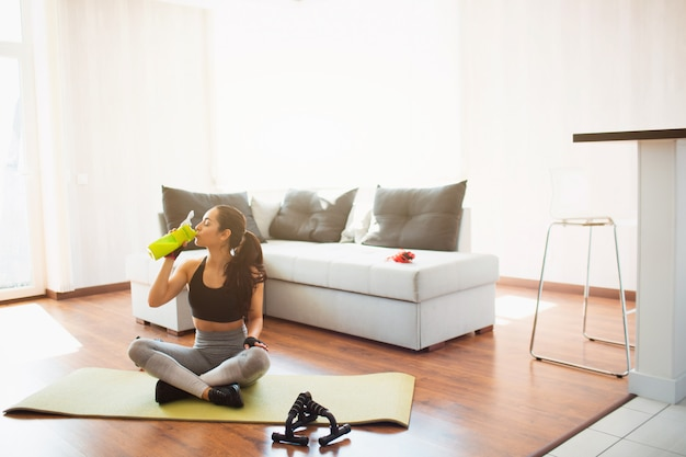 Young woman doing sport workout in room during quarantine. sit on mat with crossed legs and drink protein from green bottle. rest relax after workout.