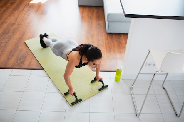 Young woman doing sport workout in room during quarantine. up side view of girl stand in plank position using push up stands hand bar. exercising in room.