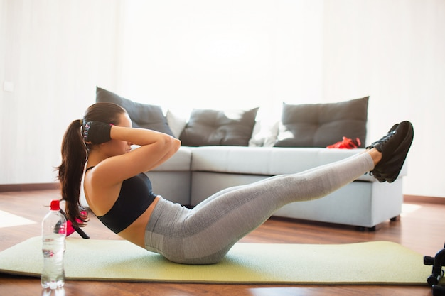 Young woman doing sport workout in room during quarantine. well built girl doing abs exercise on floor mat. keep hands close to head. hold upper and low body parts in air.