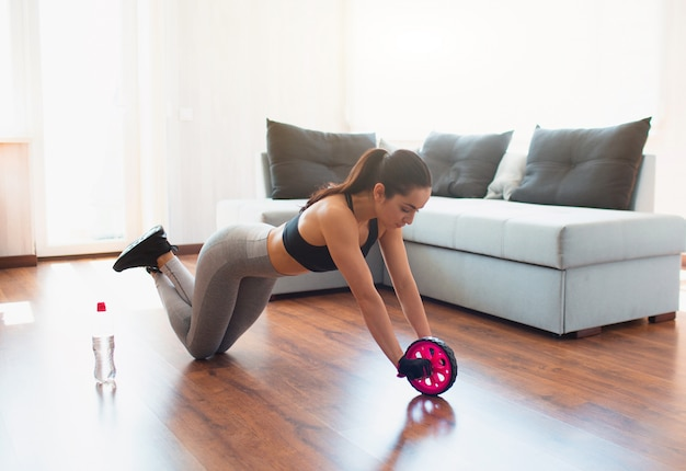 Young woman doing sport workout in room . stand on knees and using abdominal exercise roller for body stretching. home training.