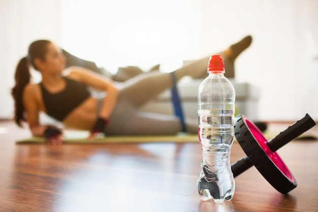 Young woman doing sport workout in room . water bottle and abdominal exercise roller in front. girl stretching and training with resistance band alone in room.