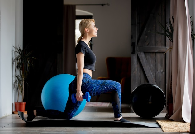 Young woman doing sports exercises with dumbbells at home
