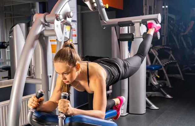체육관, 다리 및 엉덩이 운동에서 스포츠를하는 젊은 여자