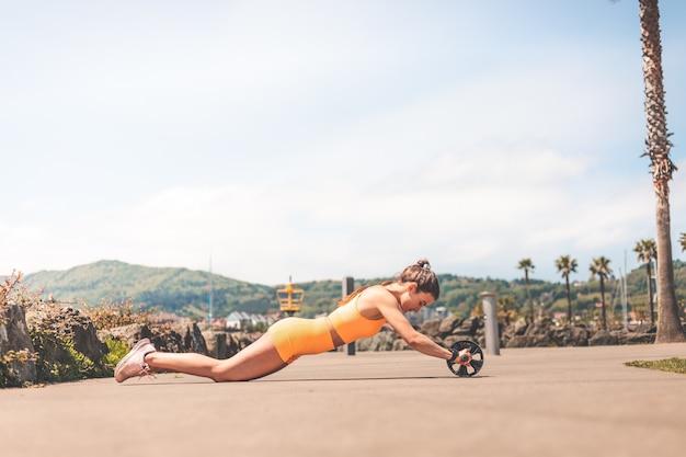 바스크 카운티 헨다이아 공원에서 주황색 스포츠 키트를 입고 운동을 하는 젊은 여성.