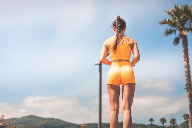 Young woman doing sports wearing an orange sports kit at the park of hendaia, basque county.