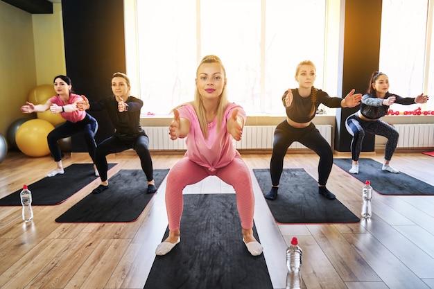 체육관에서 웅크 리고 수행하는 운동복을 입고 행에 서있는 다른 사람들과 그룹 피트니스 훈련에서 쪼그리고 운동을하는 젊은 여자