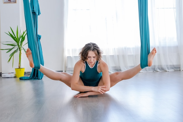 Young woman doing stretch yoga pose in gym class
